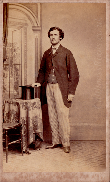 Victorian gentleman standing in front of a painted backdrop, holding a top hat