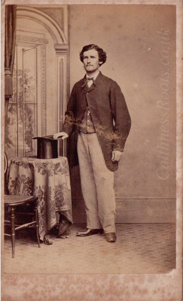 Victorian man, holding a top hat placed on a table, standing in front of a painted backdrop. Photographer James Pitt, Bethnal Green
